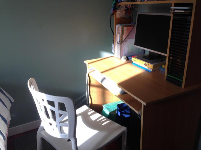 Study desk and chair in bedroom, unlimited fiber Internet available.